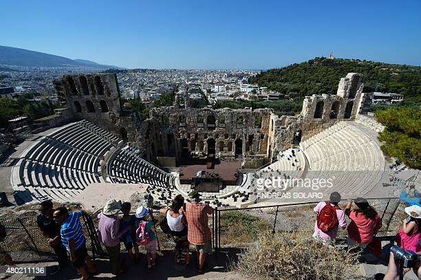 People look out over view of the city from Herodion's theatre at the Acropolis hill in downtown Athens on July 8 2015 Greece's government on July 8...