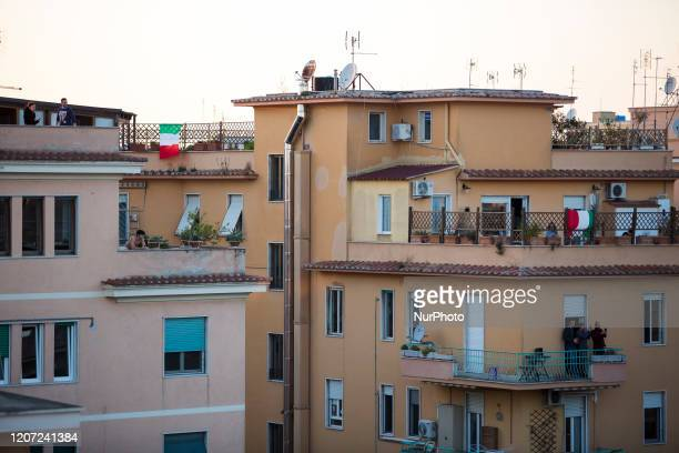 People look out the balcony of their houses during a music flash mob called ''Look out from the window, Rome mine !'' aimed at liven up the city's...