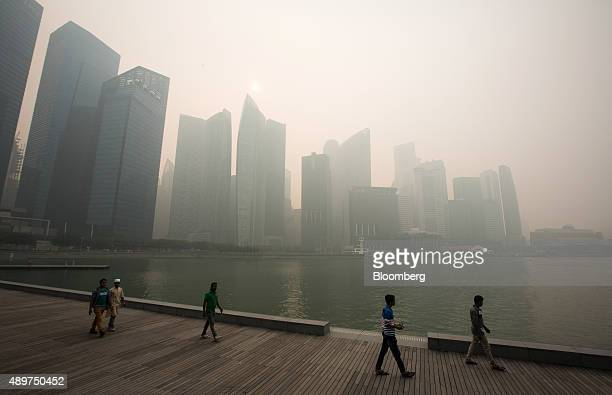 People look out towards the city skyline at Marina Bay as buildings in the central business district stand shrouded in smog in Singapore, on...