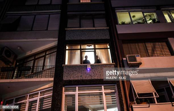 """People look outside a window as supporters of the """"No"""" march at the Kadikoy district in Istanbul on April 17, 2017 to protest following the results..."""