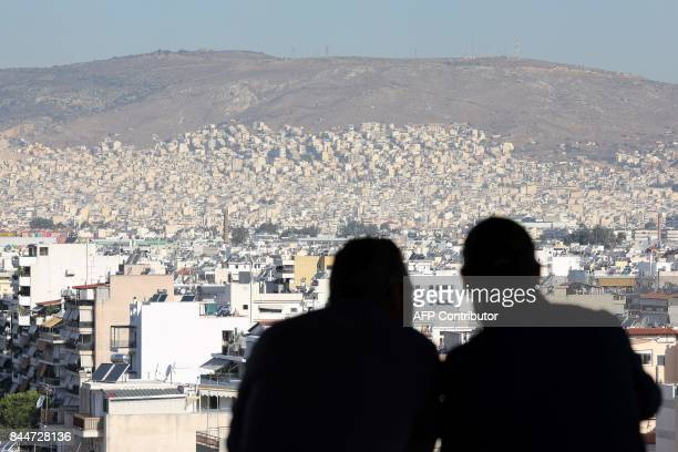 People look over the city of Athens from the terrace of the Stavros Niarchos Foundation on September 8 in Athens / AFP PHOTO / LUDOVIC MARIN