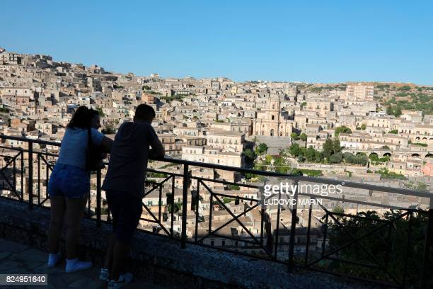 People look over the city of Modica and the Cathedral of San Giorgio Sicily on July 31 2017 Modica is part of the Italy's UNESCO Heritage Sites / AFP...