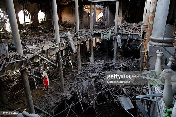 People look over the crater left by a NATO airstrike some time ago on a building at the Khamis Brigade HQ on August 29 2011 in Tripoli Libya Whilst...