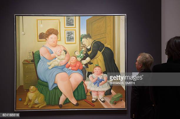 People look over the painting A Family by Fernando Botero as part of Christie's press preview of Latin American Art available at auction on November...