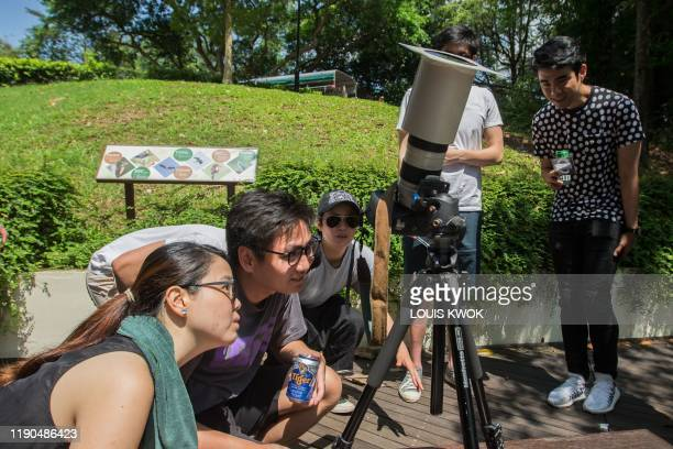 People look through a camera with a homemade solar filter to watch as the moon moves in front of the sun in a rare ring of fire solar eclipse in...