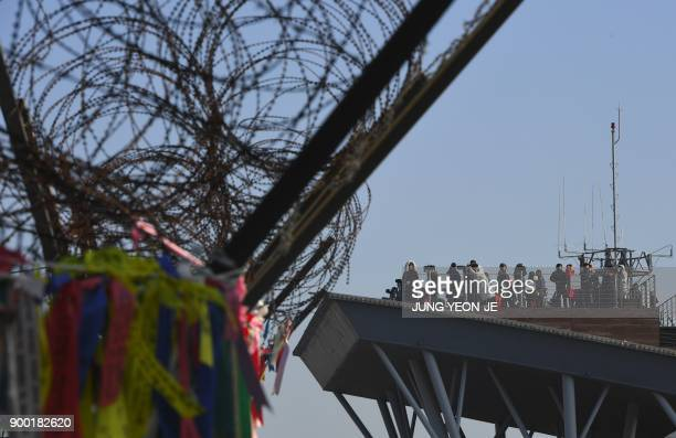 People look through binoculars at a viewing deck as a military fence is seen at the Imjingak peace park near the Demilitarized Zone dividing the two...
