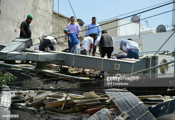 People look through debris of a building which collapsed when quake rattled Mexico City on September 19 2017 A powerful earthquake shook Mexico City...