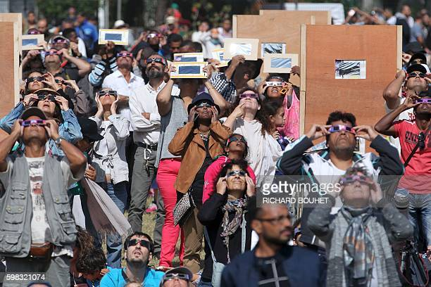 People look through eclipse viewing glasses telescopes or photo cameras an annular solar eclipse on September 1 in SaintLouis on the Indian Ocean...