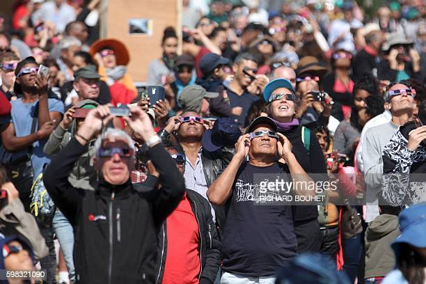 People look through eclipse viewing glasses, telescopes or photo cameras an annular solar eclipse, on September 1 in Saint-Louis, on the Indian Ocean...