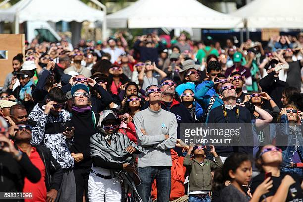 TOPSHOT People look through eclipse viewing glasses telescopes or photo cameras an annular solar eclipse on September 1 in SaintLouis on the Indian...