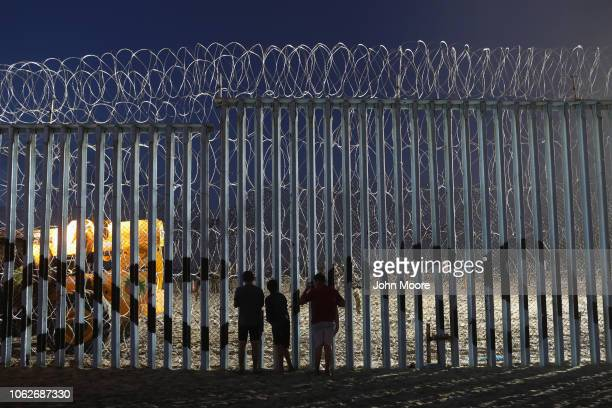 People look through the border fence on November 16 2018 in Tijuana Mexico US border agencies continued to fortify the fence with razor wire and...