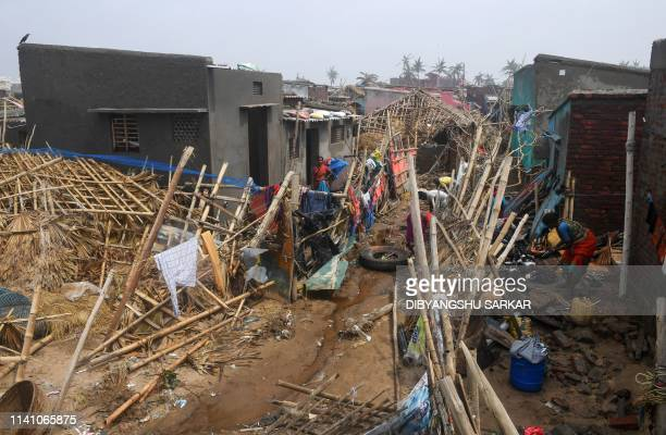 People look through the debris next to damaged buildings near the seafront in Puri in the eastern Indian state of Odisha on May 4 after Cyclone Fani...