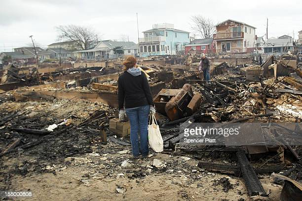People look through the remains of homes destroyed during Hurricane Sandy October 30, 2012 in the Breezy Point neighborhood of the Queens borough of...