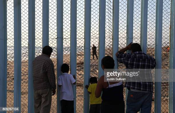 People look through the USMexican border fence at Playas de Tijuana during a Fourth of July gathering on the beach on July 4 2017 in Tijuana Mexico...