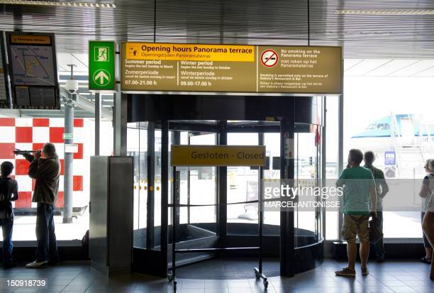 People look through windows next to a closed access to the Panorama terrace at Schiphol airport in Amsterdam on August 29 after workers found a bomb...