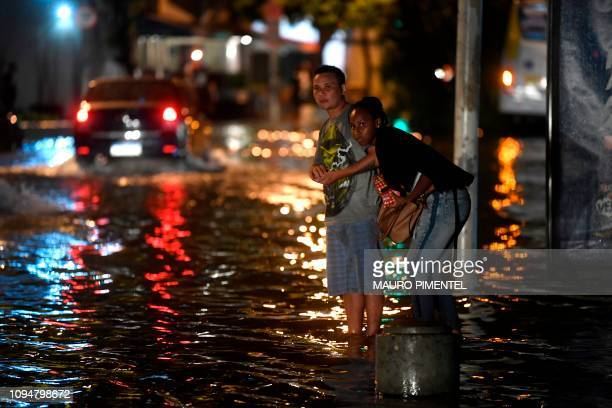TOPSHOT People look to see if a bus is coming at the Voluntarios da Patria street bus station Botafogo neighborhood after a strong rain flooded...
