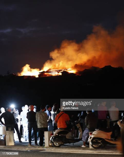 People look toward Shuri Castle in Naha Okinawa Prefecture southern Japan on the morning of Oct 31 after a fire broke out at the historic World...
