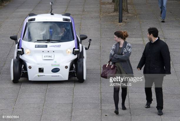 People look towards an autonomous selfdriving vehicle as it is tested in a pedestrianised zone during a media event in Milton Keynes north of London...