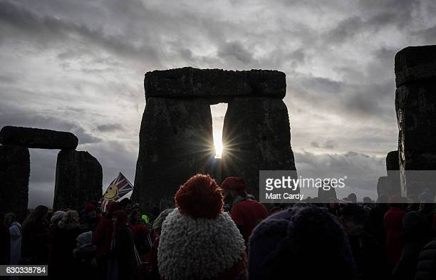 People look towards the sun as druids pagans and revellers gather at Stonehenge hoping to see the sun rise as they take part in a winter solstice...