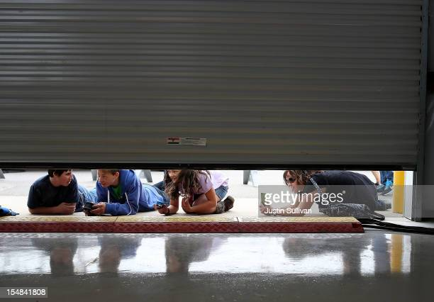 People look under a rollup door to try to see Republican presidential candidate former Massachusetts Gov Mitt Romney speaking during a campaign rally...