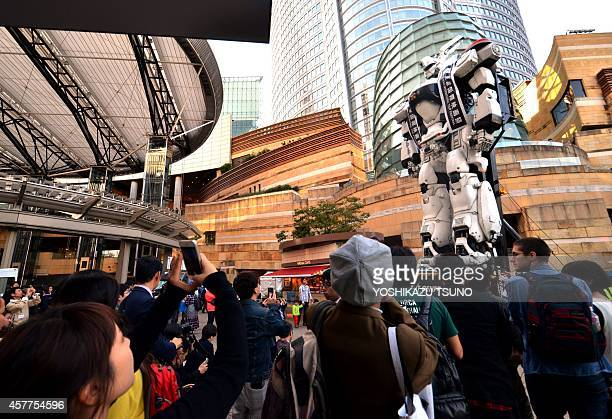 People look up as a large robot AV98 Ingram stands during the Tokyo International Film Festival at an event of Mamoru Oshii's new movie Next...