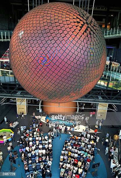 People look up at a large spherical display 'GeoCosmos' a 65meter in diameter and equipped with 1 million LED on its surface showing Mars at Japan's...