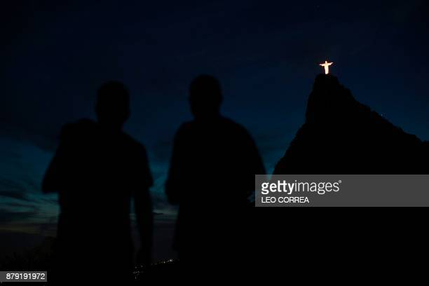 People look up at the Christ the Redeemer statue as it is lit with orange during the International Day for the Elimination of Violence Against Women...