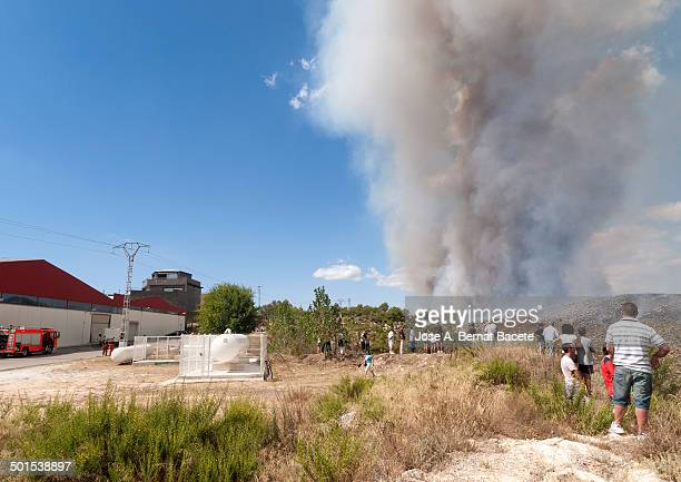 People looking at a large plume of smoke from a forest fire that advances from one area to an industrial estate canyoning.Bocairent,, Spain
