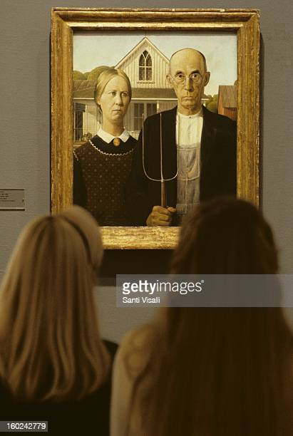 People looking at a painting of Grant Wood The American Gothic at the Art Institute in Chicago in Chicago in 1987