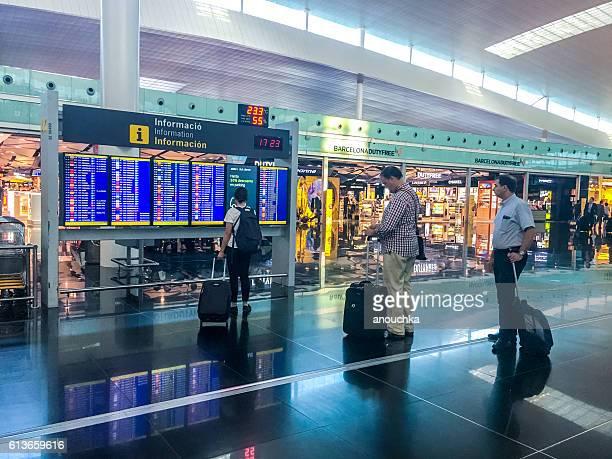People looking at flight schedule, Barcelona Airport, Spain