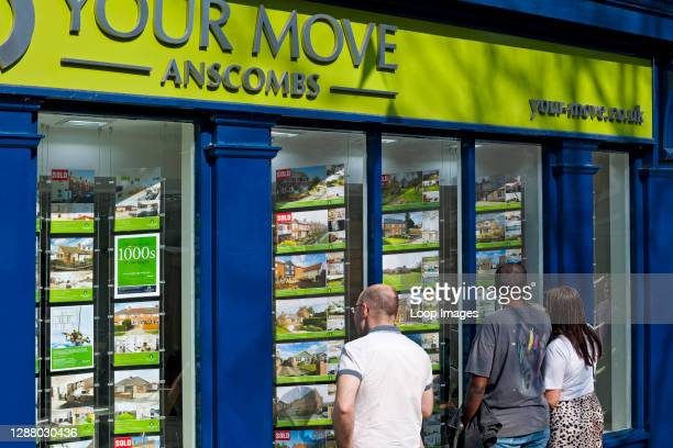 People looking at houses for sale or rent in an estate agents window.