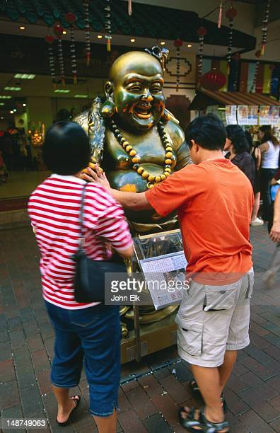 People looking at Laughing Buddha statue, Waterloo Street.