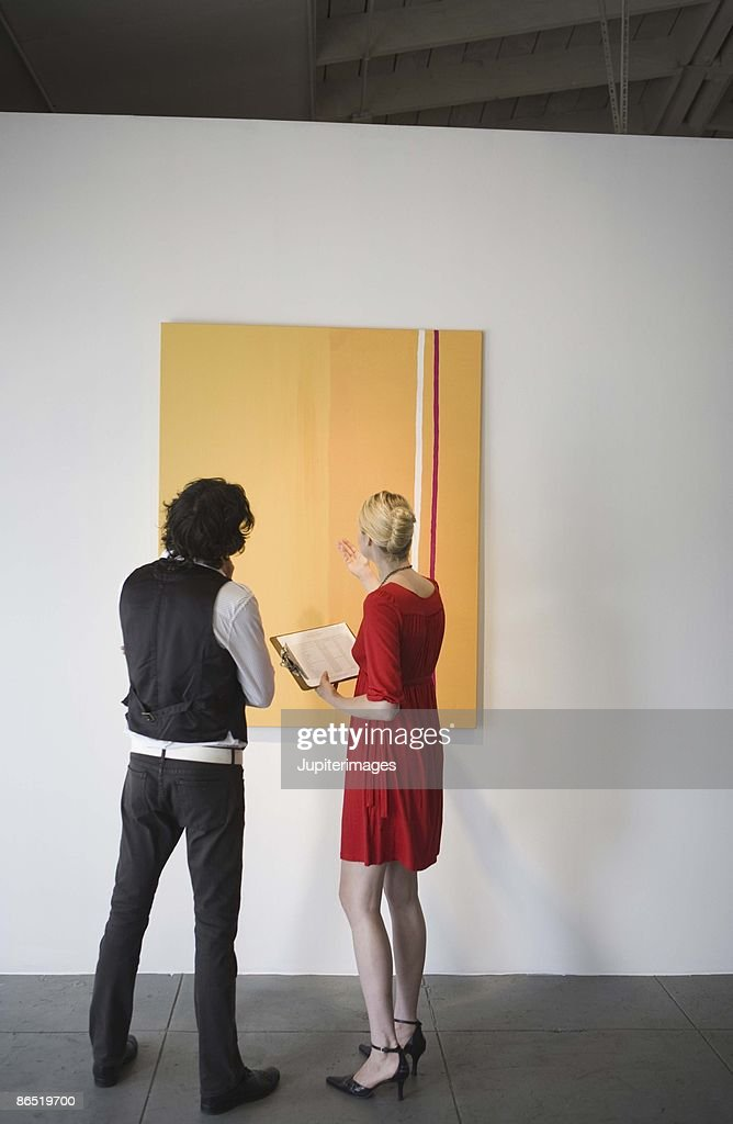 People looking at painting in art gallery : Stock Photo