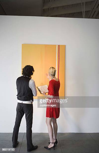 People looking at painting in art gallery