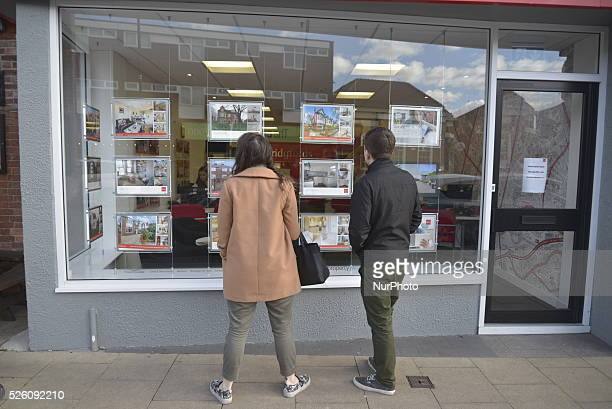 People looking at properties in the window of an estate agent in Greater Manchester, Manchester, England, United Kingdom on Monday 15th February...