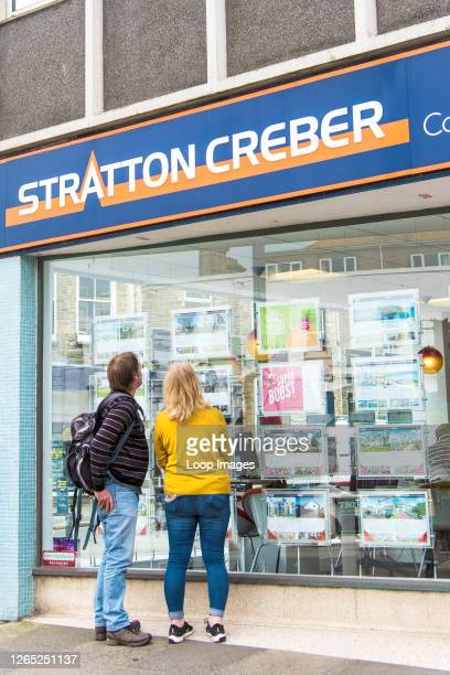 People looking at property information in a Stratton Creber Estate Agent window in Newquay town centre in Cornwall