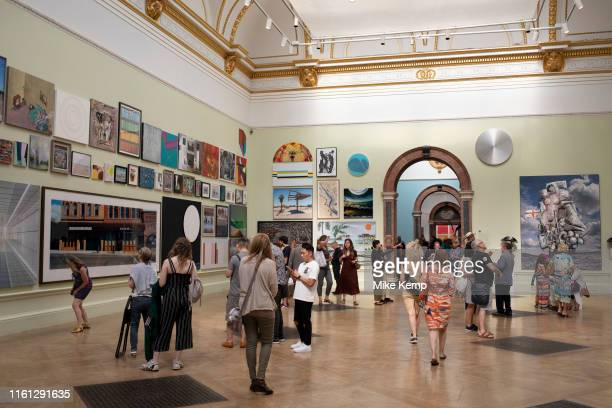People looking at the artworks in one of the main galleries at the Royal Academy for the Summer Show in London, United Kingdom. The Summer Exhibition...