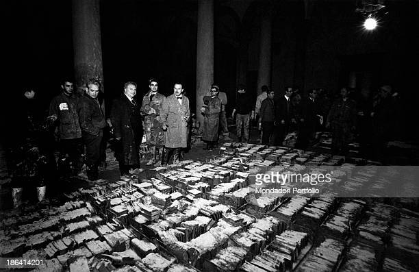 People looking at the books damaged by the flood of the Arno River Florence November 1966
