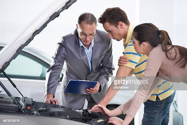 People looking at the new car engine in showroom.