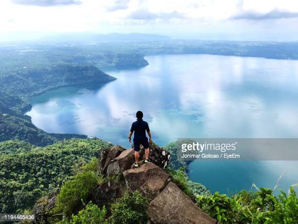 people looking at view of mountains against sky - philippinen stock-fotos und bilder