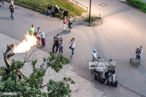 people looking at wawel dragon spitting fire in krakow, poland seen from above during summer night - wawel cathedral stock pictures, royalty-free photos & images