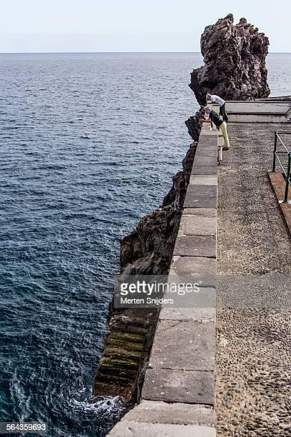 people looking down to sea from fort ruin - merten snijders stockfoto's en -beelden