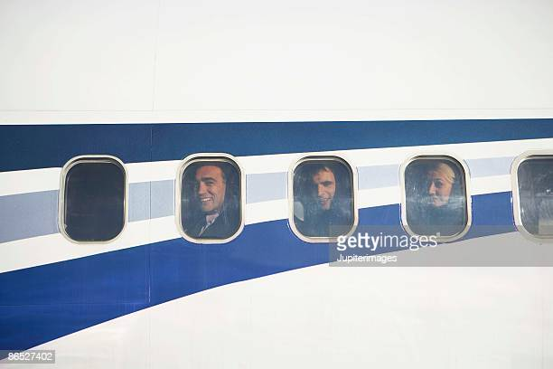 People looking out windows of airplane