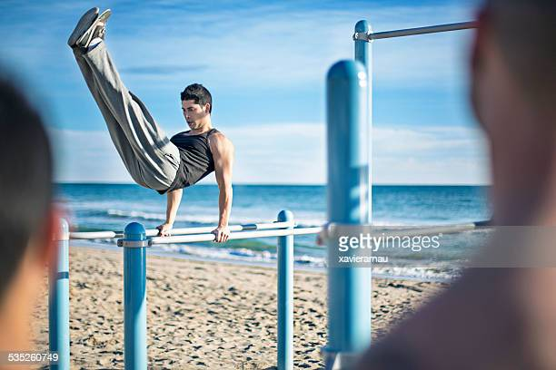 people looking their friend working out in the beach - toughness stock pictures, royalty-free photos & images