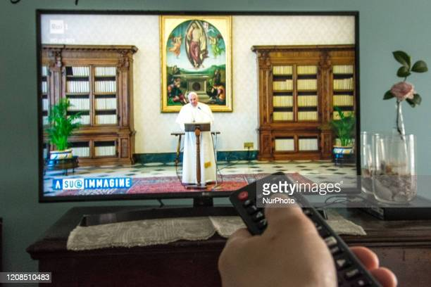 People looks on TV Pope Francis celebrates mass from Santa Marta in Rome Italy on March 29 2020