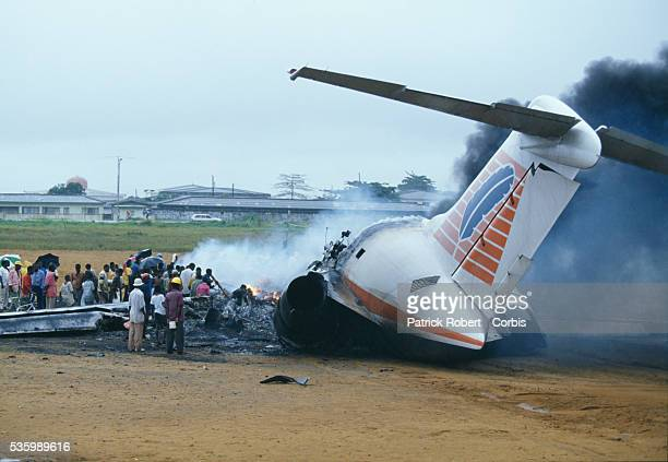 People loot a crashed ADC company plane at the airport in Monrovia in August 1994 during the Liberian Civil War