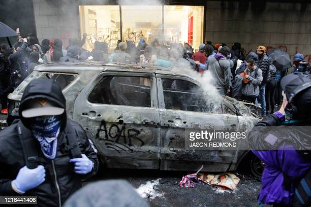 People loot a Nordstrom store near a burned police car following demonstrations protesting the death of George Floyd, a black man who died May 25 in...