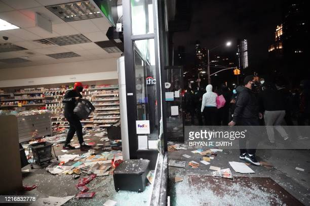 People loot a store during demonstrations over the death of George Floyd by a Minneapolis police officer on June 1, 2020 in New York. - New York's...