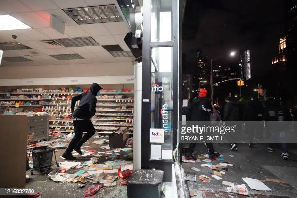 People loot a store during demonstrations over the death of George Floyd by a Minneapolis police officer on June 1 2020 in New York New York's mayor...