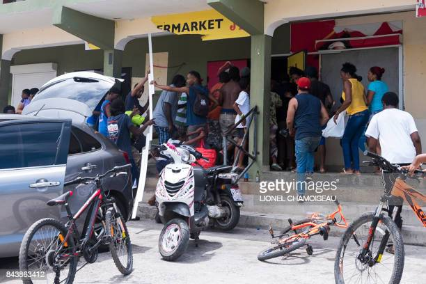 People loot a store on September 7 2017 in Quartierd'Orleans on the French Carribean island of SaintMartin after the passage of Hurricane Irma France...